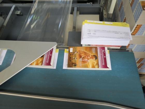 Bok og faktura legges klare for å «plastes», slik at pakken vil tåle transport i posten.