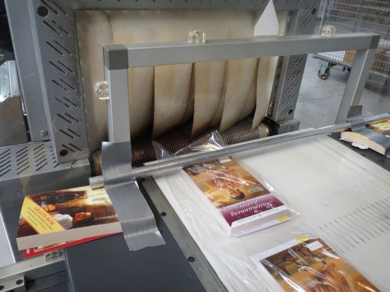 Boken sendes inn i en maskin som sørger for at plasten sitter godt rundt pakken.