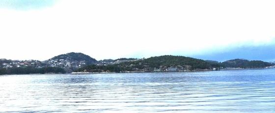 Her er bildet illustratøren fikk tilsendt som bakgrunnsmateriale for seilskutescenen på forside 13. Det er Grimstadfjorden sett fra Hopsvika/Hope (jmf. handling i begynnelsen av bok 8).  Fjellene i bakgrunnen er faktafeil, og det tar jeg på min kappe. Det er tegnet etter et foto jeg tok på Hope, så dette er i Grimstadfjorden som er en avstikker i den ruten Lucie og de andre seilte fra Bergen til Fana. Men det skulle bare være noen fjell.  (Foto: May Lis Ruus)