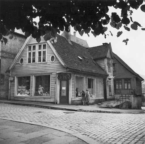 Marken 1 i 1957. Det har i nyere tid vært både barneklærforretning, pelsverksted- og butikk og klesbutikk i huset. (Foto: Gustav Brosing / UBB-Bros-00245A)