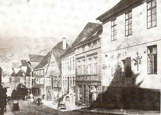 Audunsgården merket med 1609 (steinbygningen til høyre) var Bergens postkontor fra 1647 til 1702, og sannsynligvis også Weldings vinkjeller. Gården var opprinnelig eid av Jon Smør, ridder og slottsherre på Bergenhus 1472-83. Gården ble ødelagt i storbrannen i 1916 og etter reguleringen forsvant almenningen. (Fotografiet er i Postmuseets eie, årstall ukjent, men før bybrannen 1916.) (Kilde: Wikipedia, CC-lisens)